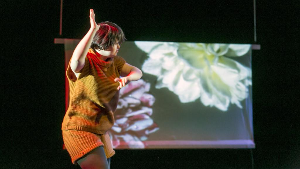 Szene aus einer Auffuehrung: Eine Frau im gelben Strickkleid tanzt vor einer Leinwand auf der große Blueten zu sehen sind