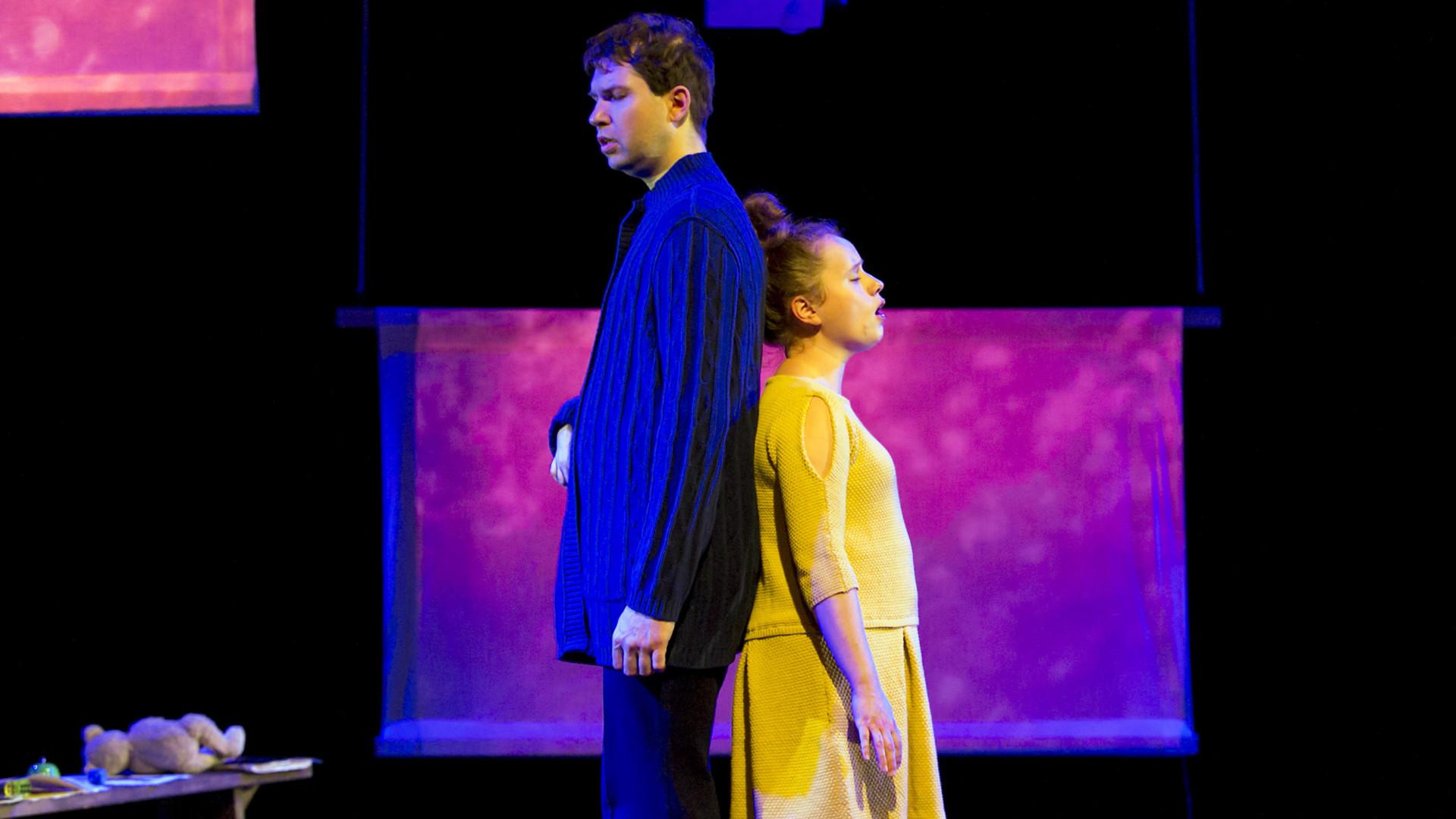 Szene aus einer Auffuehrung: Ein Mann und eine Frau stehen mit geschlossenen Augen Ruecken an Ruecken