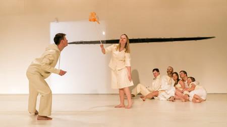 Szenenfoto aus einer Aufffuehrung: Links steht mit geknicktem Oberkörper ein Mann, der ein Stück orangefarbenen Stoff beobachtet, den eine Frau rechts mit einem Stoch durch die Luft schleudert. Im Hintergrund sitzt eine Gruppe Menschen. Alle tragen weiße Kleidung.