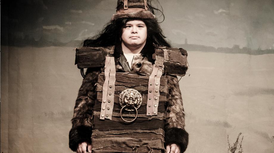 Ein Mann mit langen Haaren in einem archaischen Haeuptlingskostuem