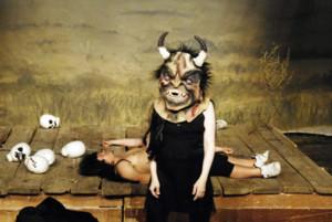 Szenenfoto aus einer Auffuehrung: Eine Person mit einer Teufelsmaske m Vordergrund. Im Hintergrund liegt eine Person. Neben hr Totenkoepfe.