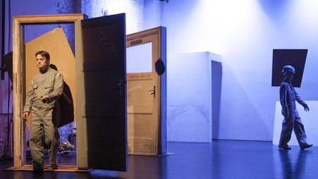Szenenfoto aus einer Auffuehrung: Links eine offene Holztuer, die ein Mann im Overall durchschreitet. Rechts im Hintergrund eine Frau im Overall mit einem rechteckigen Gebilde am Kopf.