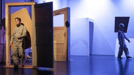 Szenenfoto aus einer Aufführung: Links eine offene Holztür, die ein Mann im Overall durchschreitet. Rechts im Hintergrund eine Frau im Overall mit einem rechteckigen Gebilde am Kopf.