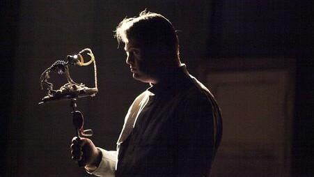 Szenenfoto aus einer Aufführung: Ein junger Mann im Profil im Halbdunkel. Er hat ein seltsames rundes Gebilde