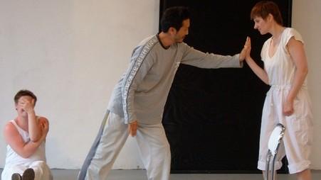 Szenenausschnitt: Im Vordergrund beruehren sich zwei Personen mit den Haenden. Im Hintergrund sitzt ein Performer an die Wand gelehnt und haelt sich die Hand vor das Gesich