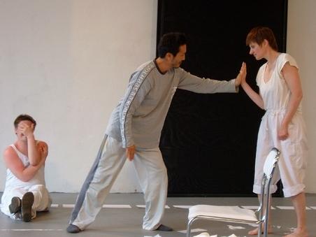 Szenenausschnitt: Im Vordergrund berühren sich zwei Personen mit den Händen. Im Hintergrund sitzt ein Performer an die Wand gelehnt und hält sich die Hand vor das Gesich