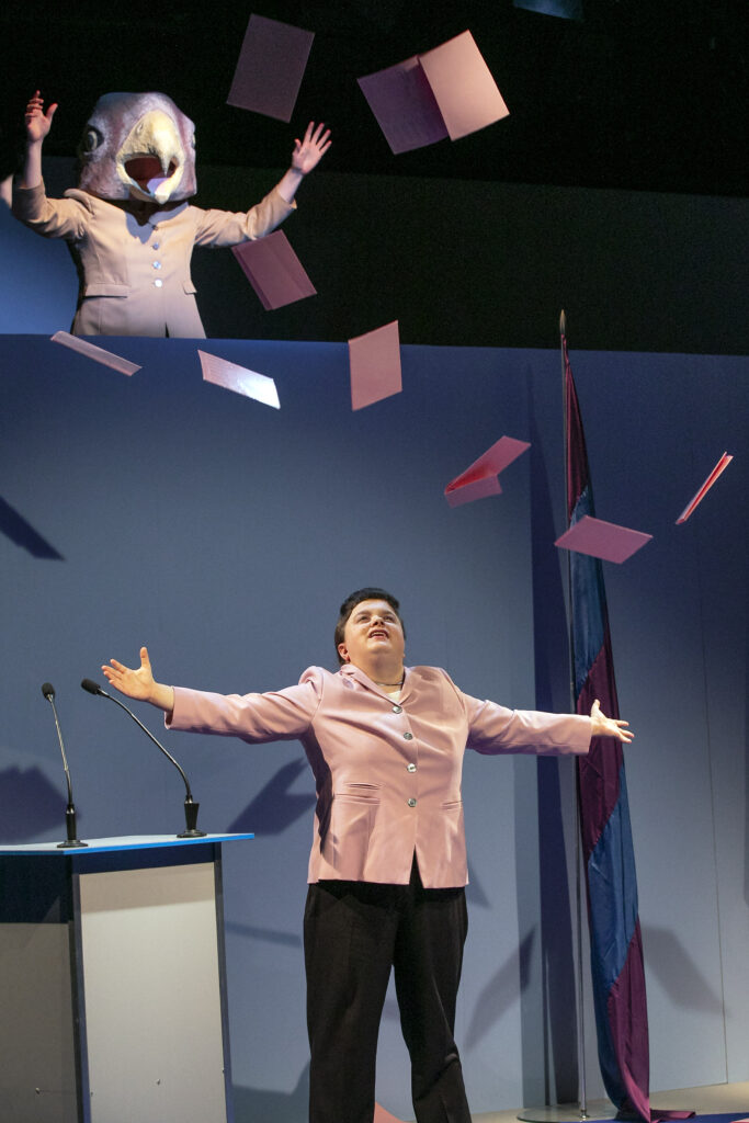 Scene photo of a performance: Upstairs a person mit eagle mask. downstairs a woman with wide spread arms. It is raining ballot paper.