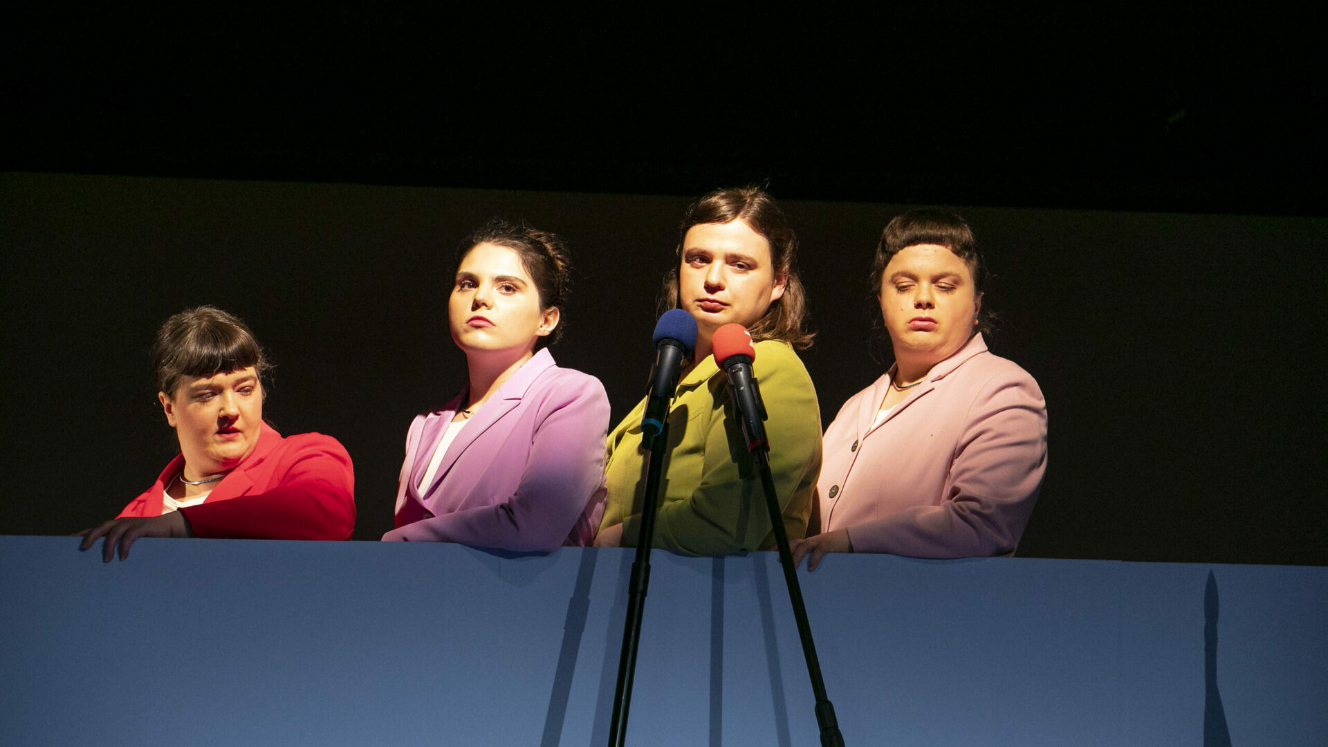 Scene photo of a performance: 4 women on a stage wearing blazers standing behind each other.