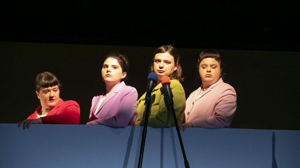 Szenenfoto einer Auffuehrung: Vier Frauen einer einer Bühne in Blazern hintereinander.