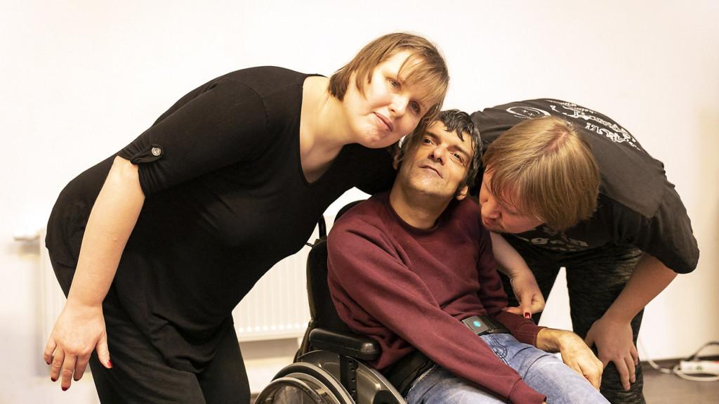 Workshopsituation: Ein Mann im Rollstuhl. Eine Frau und ein Mann beugen sich zu ihm.