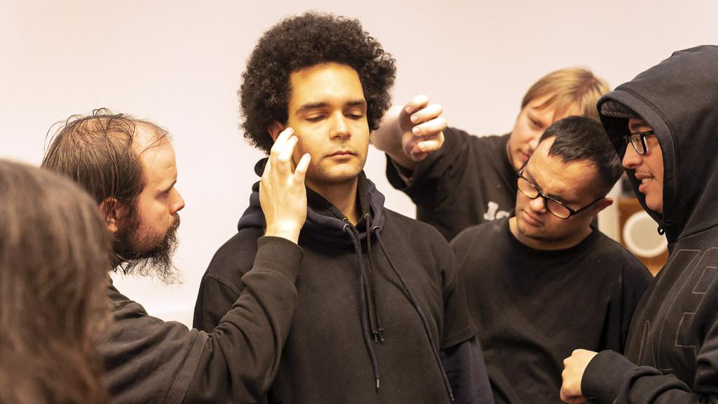 Workshopsituation: Ein Mann mit geschlossenen Augen. Sein Gesicht wird von mehreren anderen Menschen mit den Haenden beruehrt