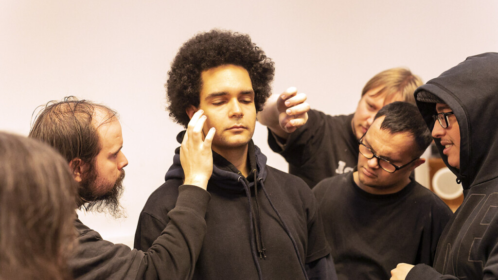 Workshopsituation: A man with closed eyes. His face is touched b other people, who are also in the photo.