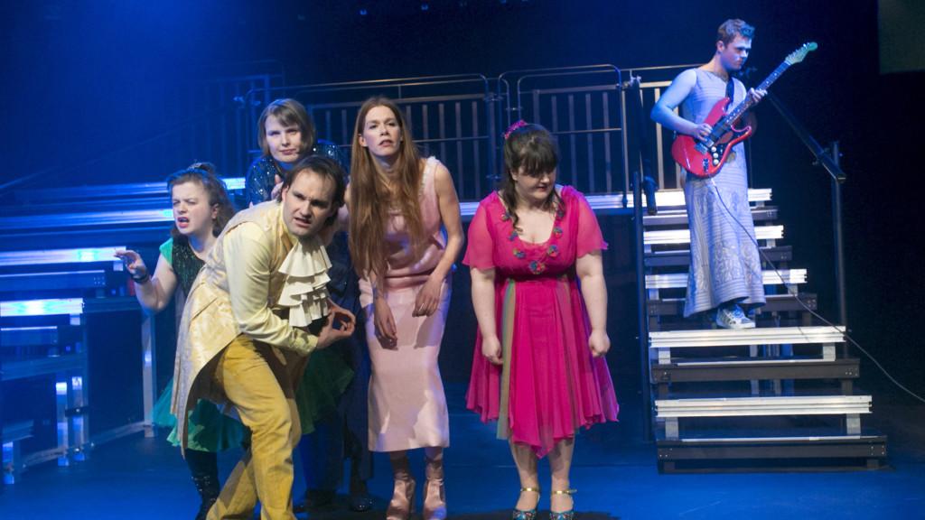 Szenenfoto aus einer Auffuehrung: Vier Personen gebeugt auf einer Bühne. Im Hintergrund einen Person mit Gitarre.