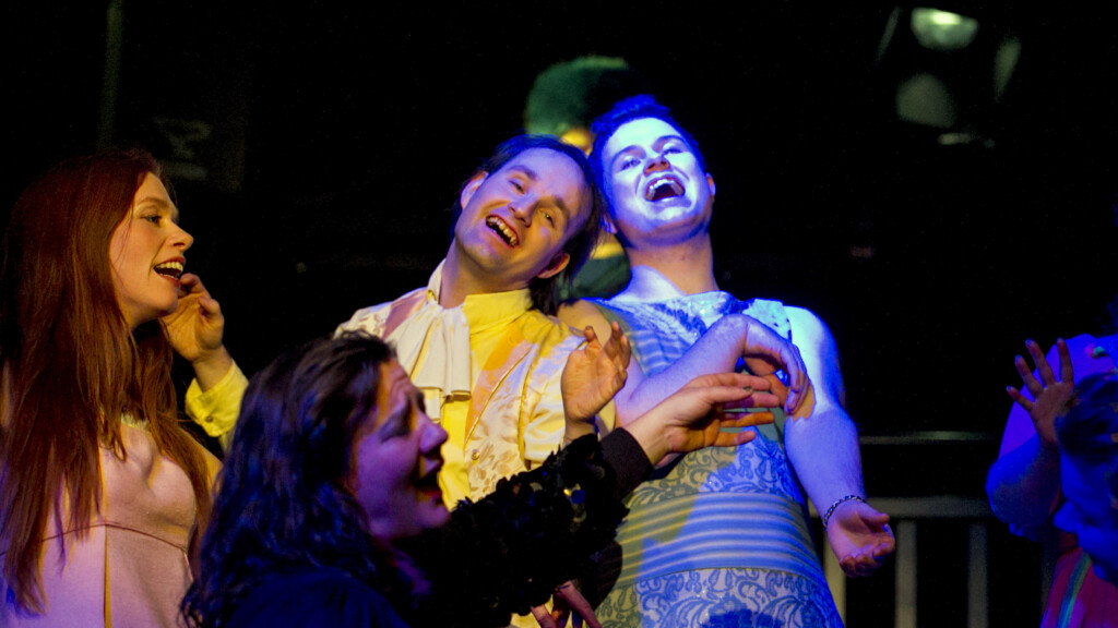 Scene photo of a performance: Three people are laughing on a stage.