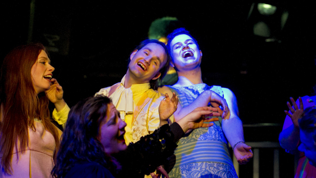 Szenenfoto aus einer Auffuehrung: Drei Personen lachend auf einer Theaterbuehne.