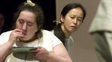 Szenenfoto aus einer Auffuehrung: Zwei Frauen. Eine isst etwas von einem Teller. Die andere beobachtet sie dabei