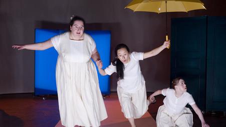 Szenenfoto aus einer Auffuehrung: Drei Frauen, weiß gekleidet. Eine hat einen gelben Regenschirm
