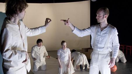 Szenenfoto aus einer Aufführung: Zwei Männer stehend im Vordergrund mit ausgestreckten Armen. Mehrere knieende Menschen im Hintergrund