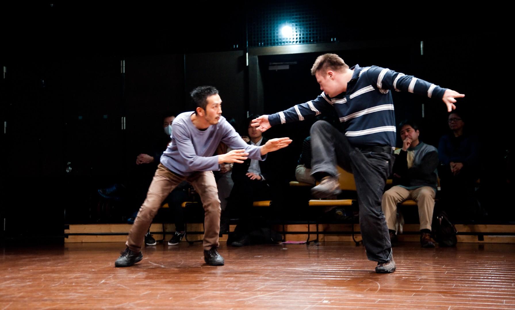 Szenenfoto einer Aufführung: Zwei Männer in Alltagskleidung tanzen.