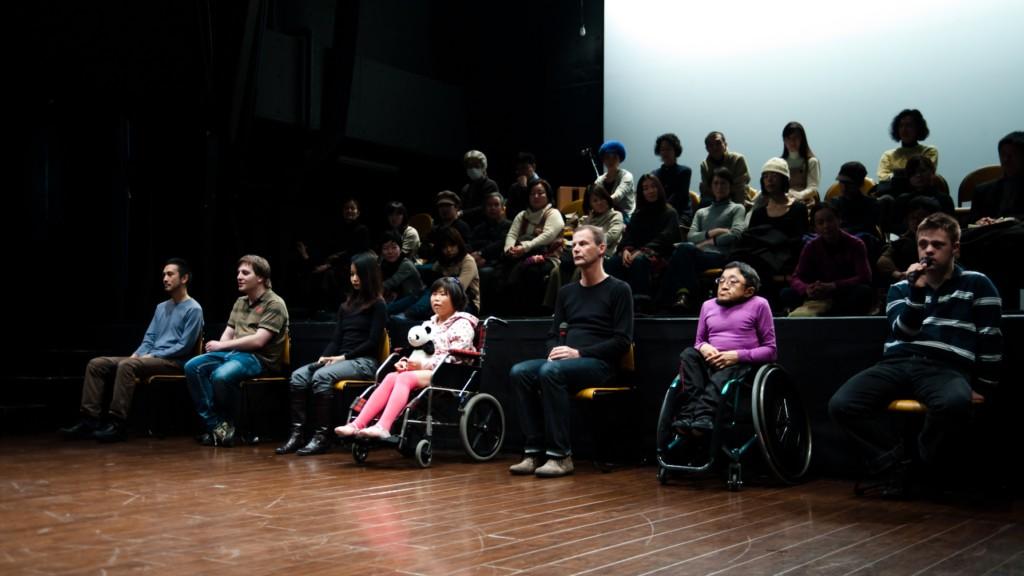 Szenenfoto aus einer Auffuehrung: Sechs Personen, teilweise im Rollstuhl, sitzen in Alltagskleidung in einer Reihe. Manche haben Mikrofone in der Hand. Dahinter sitzt Publikum auf einer Tribuene