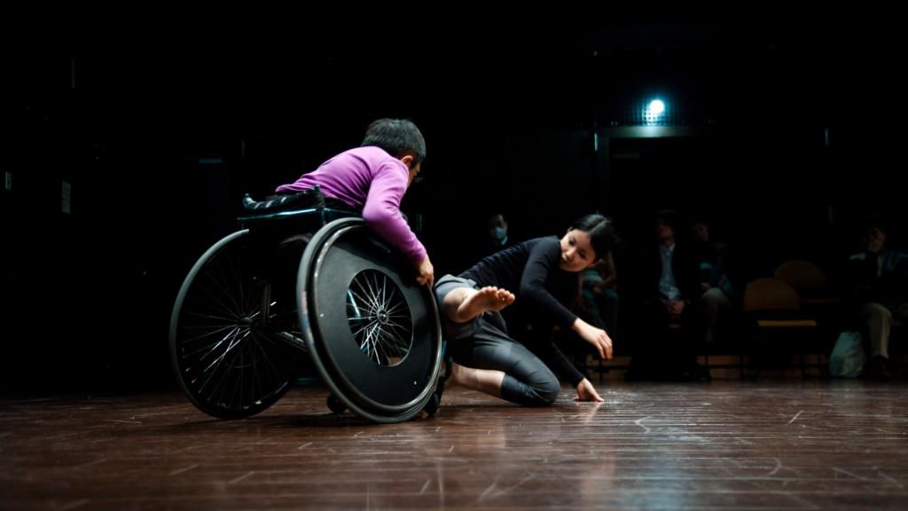 Szenenfoto aus einer Auffuehrung: Ein Mann im Rollstuhl und eine junge Frau tanzen akrobatisch