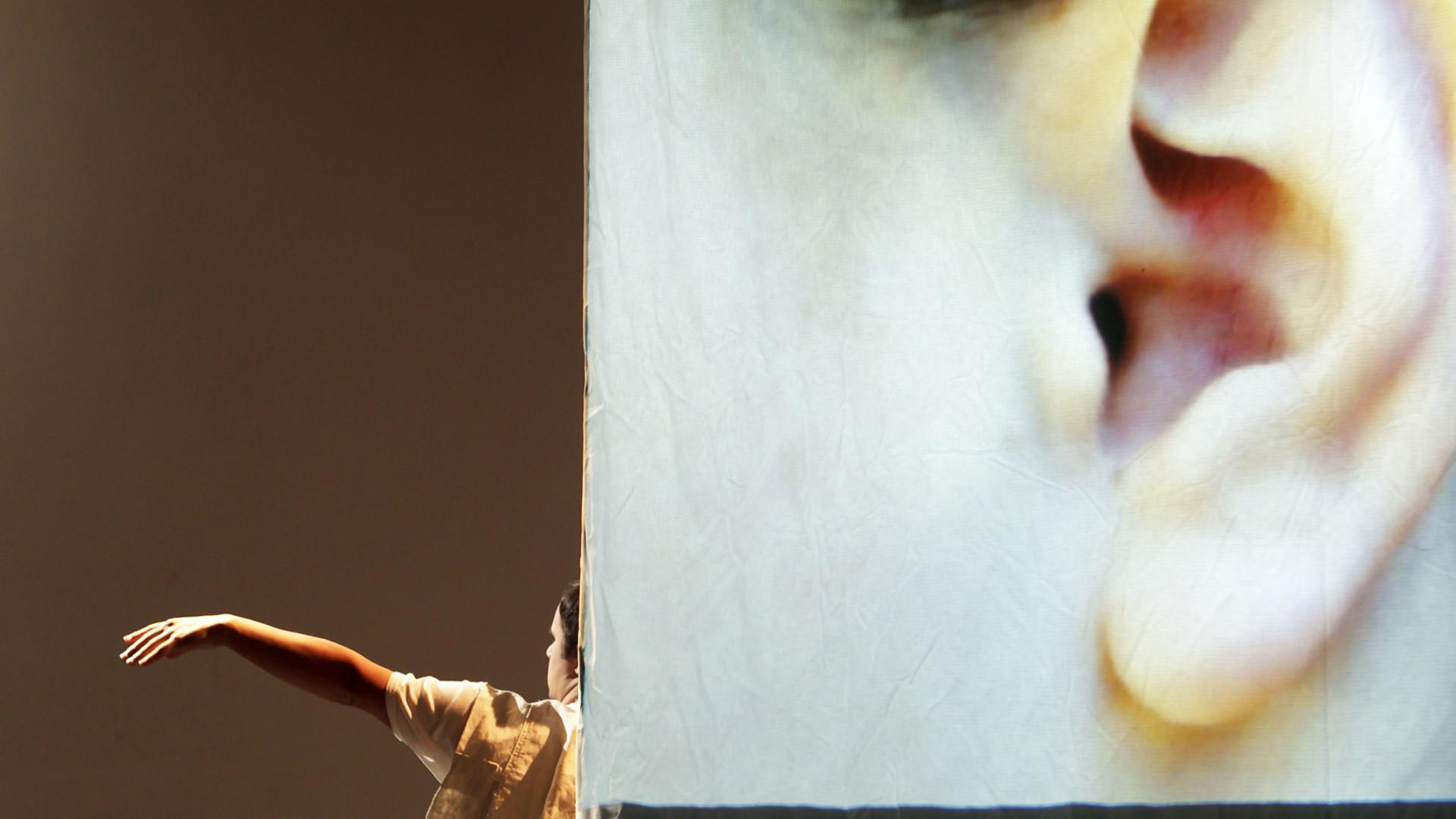Szenenfoto aus einer Auffuehrung: Eine Großprojektion eines menschliches Ohres. Links daneben klein ein Taenzer, von dem nur der ausgestreckte Arm und der halbe Koerper zu sehen ist.