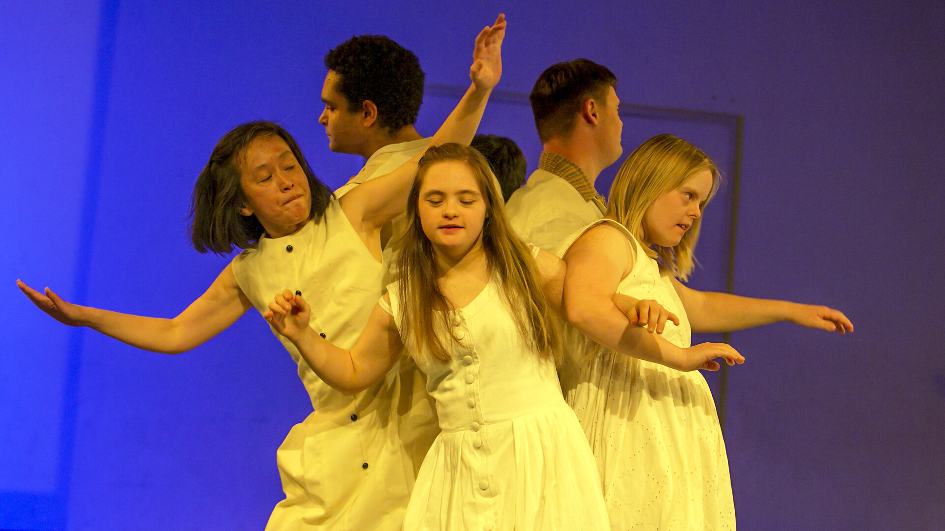 A group of dancers wearing white clothes in front of a blue background.