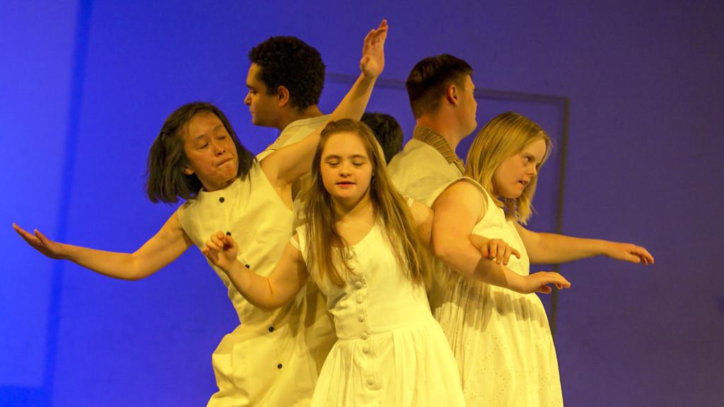Szenenfoto aus einer Auffuehrung: Eine Gruppe von weiß gekleideten TaenzerInnen vor blauem Hintergrund