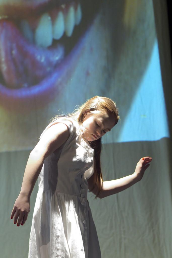Szenenfoto aus einer Auffuehrung: Eine Frau im weißen Kleid tanzt vor einer Projektion auf der ein Mund mit herausgestreckter Zunge zu sehen ist.