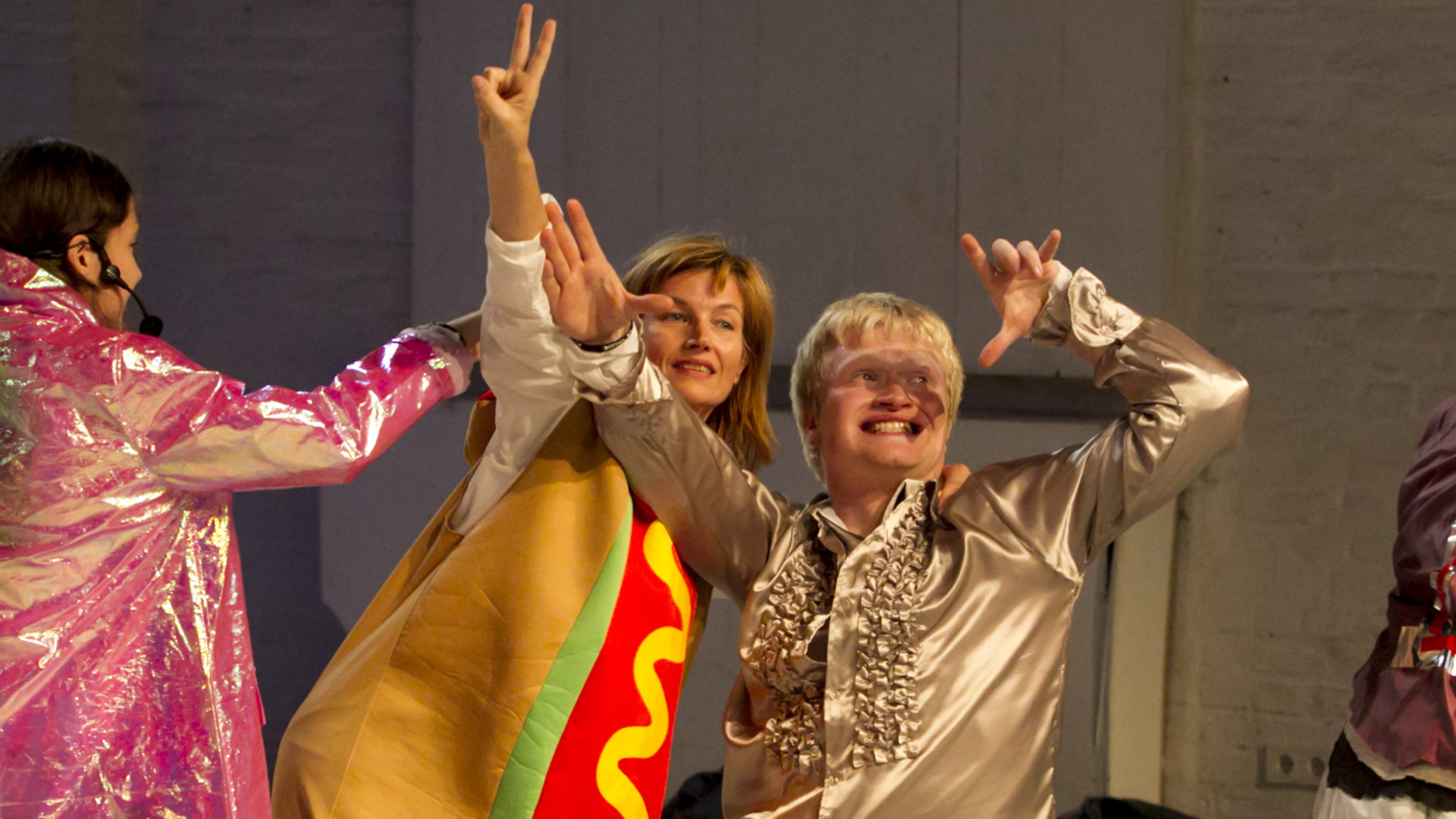 Szenenfoto: Drei Personen tanzen froehlich in bunten Kostuemen. Eine Fau zeigt das Peacezeichen
