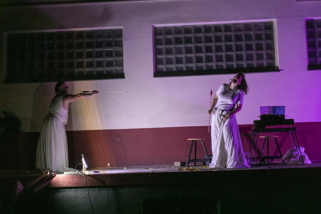 Szenenfoto aus einer Auffuehrung: Zwei Personen auf einer Buehne. Eine mit Pfeil und Bogen.