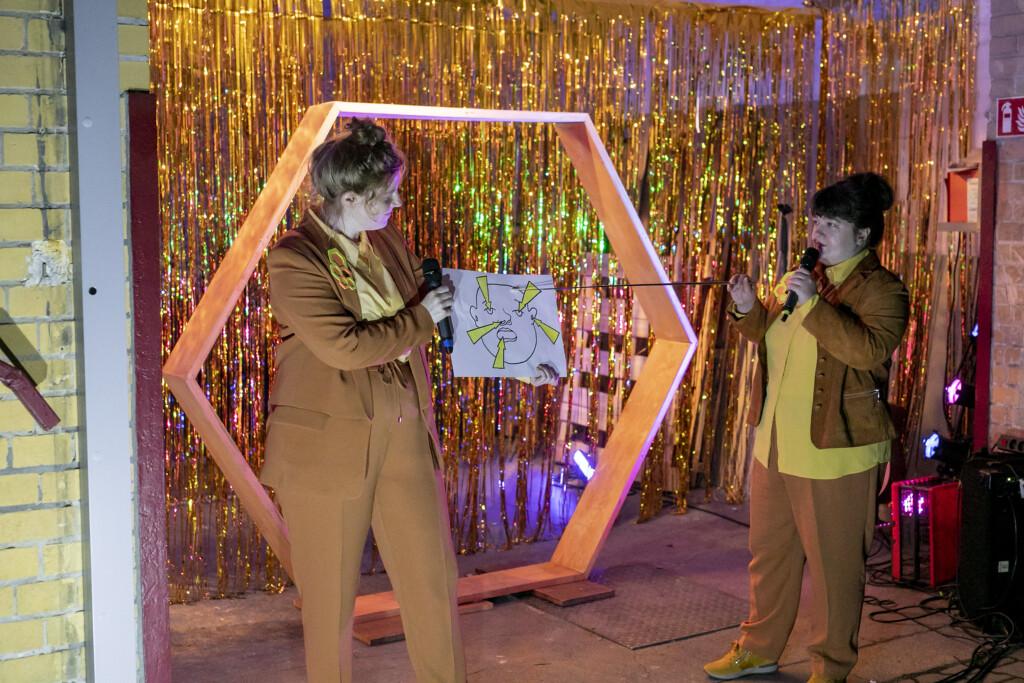 Szenenfoto aus einer Auffuehrung: Zwei personen vor einem goldenen Vorhang auf einer Theaterbuehne.