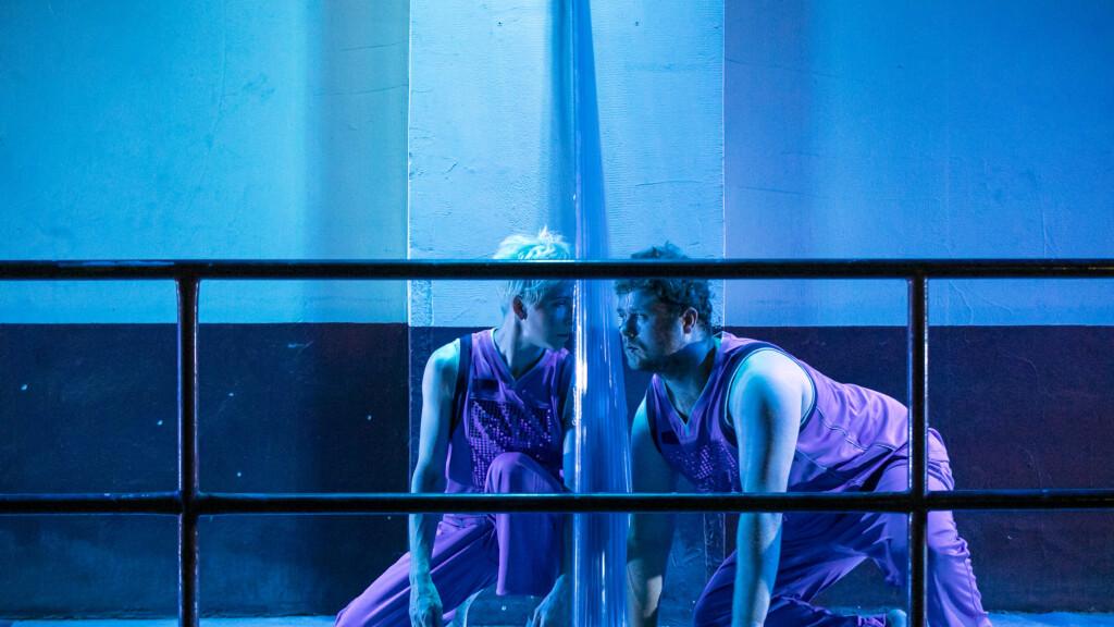 Szenenfoto aus einer Auffuehrung: Zwei Personen tanzen. In der Mitte eine Art Plexiglasscheibe.