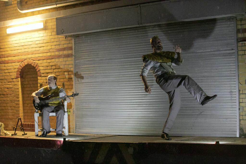 Szenenfoto aus einer Auffuehrung: Zwei maenner auf einer Buehne.