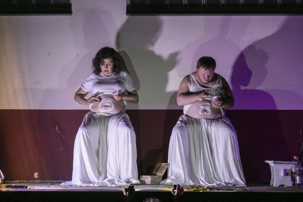 Szenenfoto aus einer Auffuehrung: Ein Mann und eine Frau auf einer Buehne betrachten ihre Baeuche.