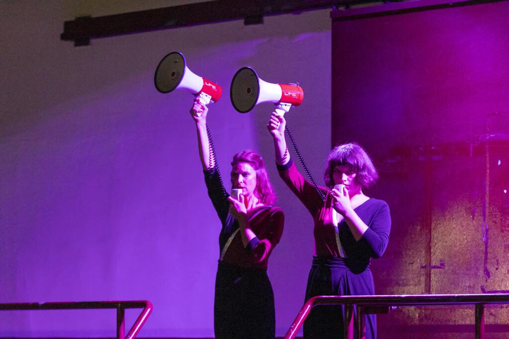 Szenenfoto aus einer Auffuehrung: Zwei Personen mit Megafonen