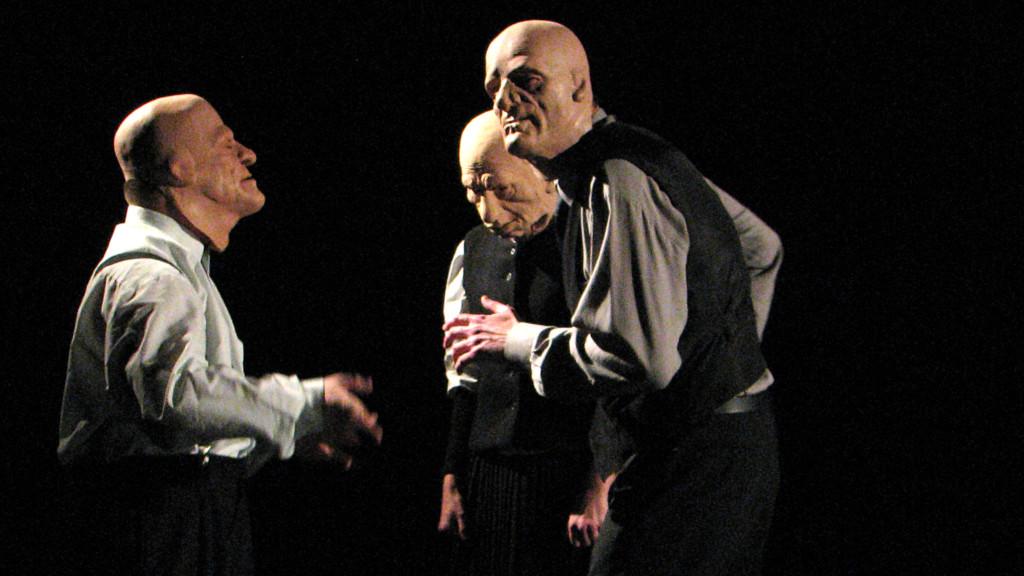 Szenenfoto: Drei Maenner mit Gummimasken stehen sich gegenüber.