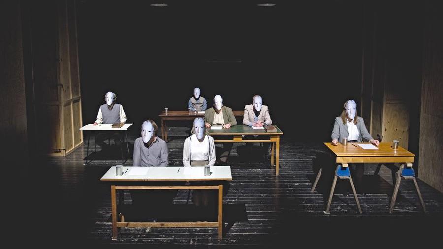 Szenenfoto: Sieben Personen mit Masken auf den Gesichtern sitzen an mehreren Tischen