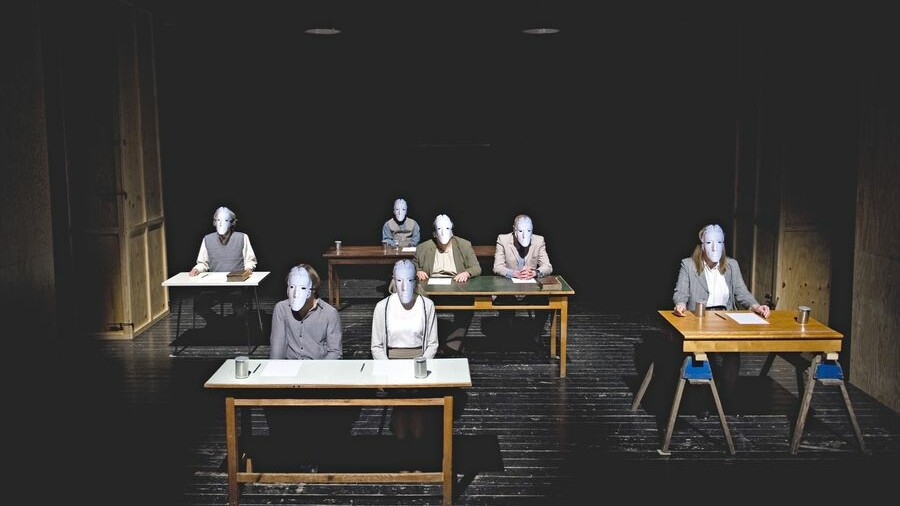 Scene photo of a performance: Seven people are sitting on office tables on a stage wearing masks.