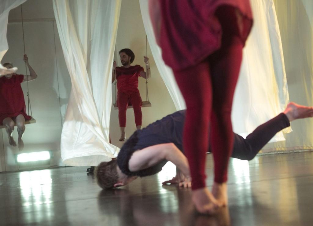 Szenenfoto: Ein Mann dreht sich am Boden, im Vordergrund sind Beine zu sehen, im Hintergrund zwei Menschen auf Schaukeln, die zwischen weißen Vorhaengen schaukeln