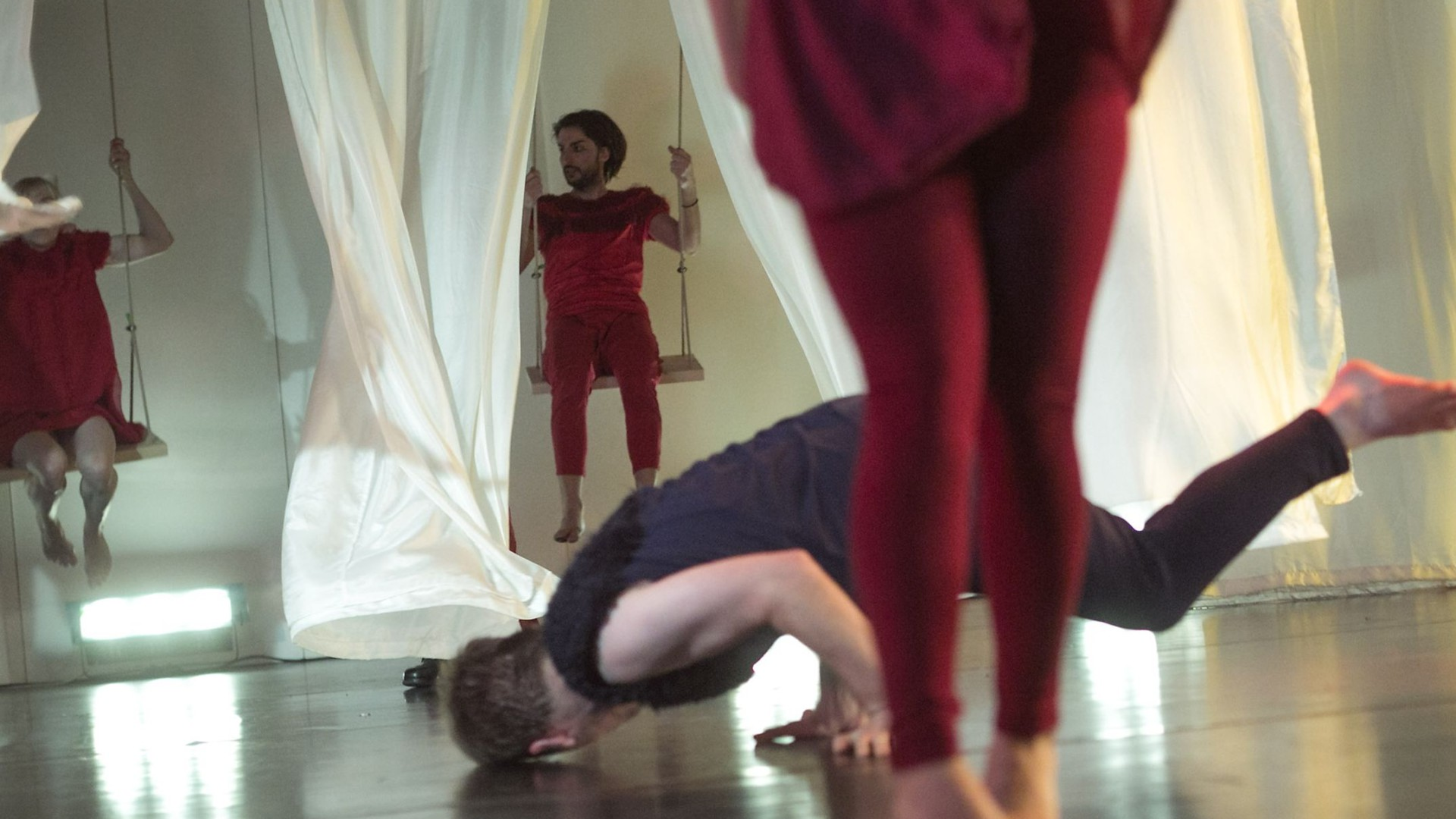 Szenenfoto: Ein Mann dreht sich am Boden, im Vordergrund sind Beine zu sehen, im Hintergrund zwei Menschen auf Schaukeln, die zwischen weissen Vorhaengen schaukeln
