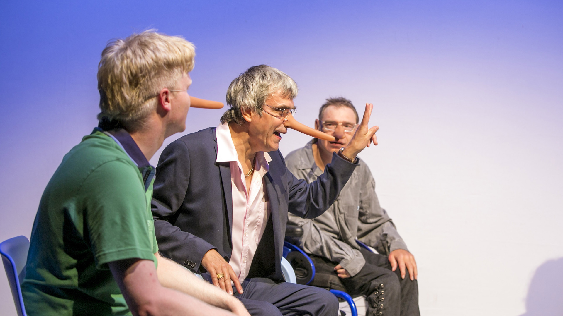 Szenenfoto: Drei Maenner sitzen debattierend auf Stuehlen. Sie tragen im Gesicht lange Pinocchio-Nasen aus Plastik.