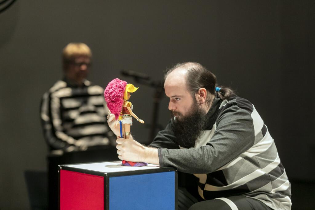 Pressefoto: Mann betrachtet Puppe auf einer Buehne