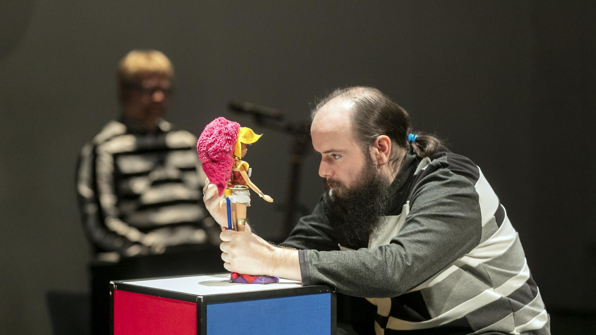 Szenenfoto einer Auffuehrung: Ein Mann schaut eine Puppe an auf einer Buehne