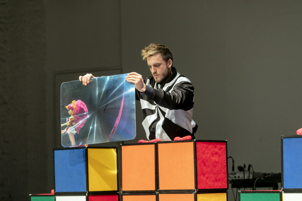 Szenenfoto einer Auffuehrung: Ein Mann mit einer Art Lupe auf einer Theaterbühne.
