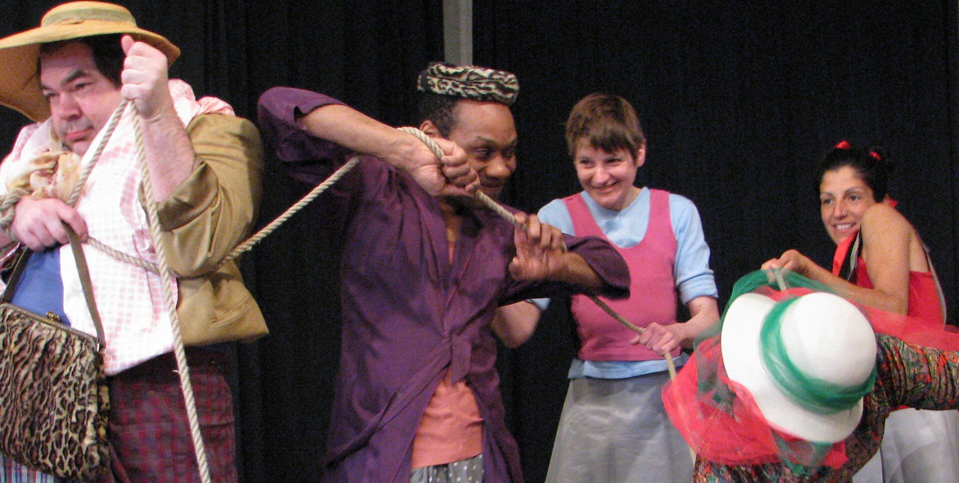 Szenenfoto einer Auffuehrung: Vier Personen nebeneinander auf einer Bühne