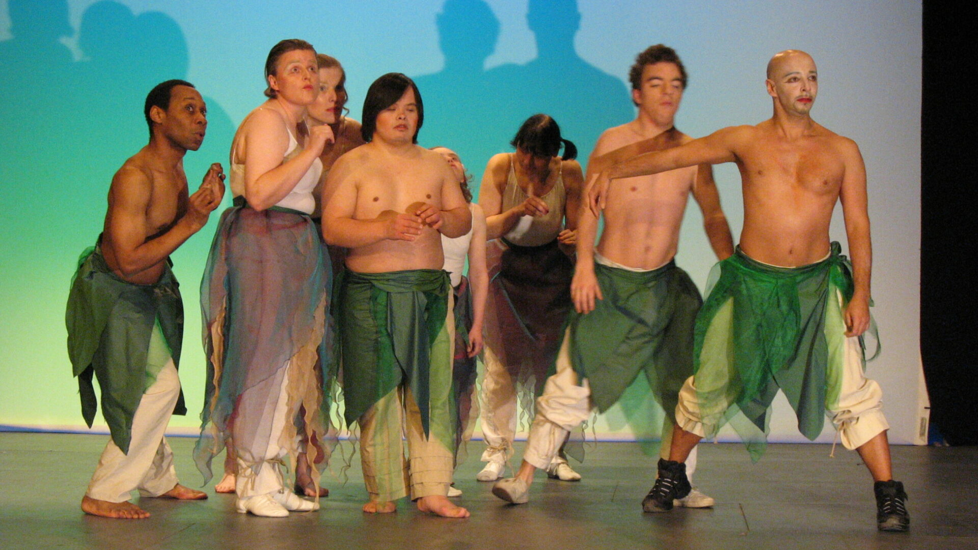 Szenenfoto einer Auffuehrung: Mehrere Performer:innen auf einer Buehne