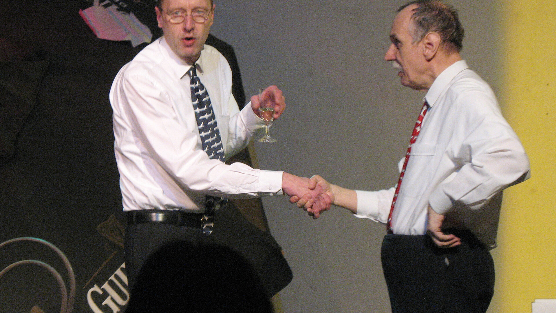 Szenenfoto einer Auffuehrung: Zwei Maenner geben sich die Hand auf einer Buehne.
