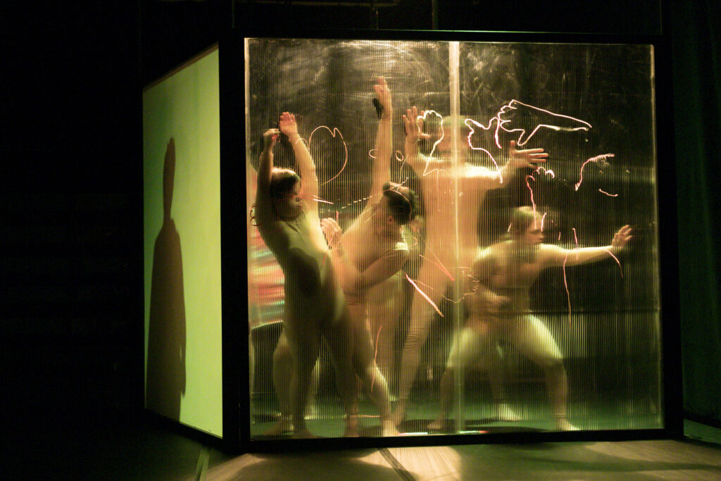 scene photo of a performance: four people behind a transparent wall.
