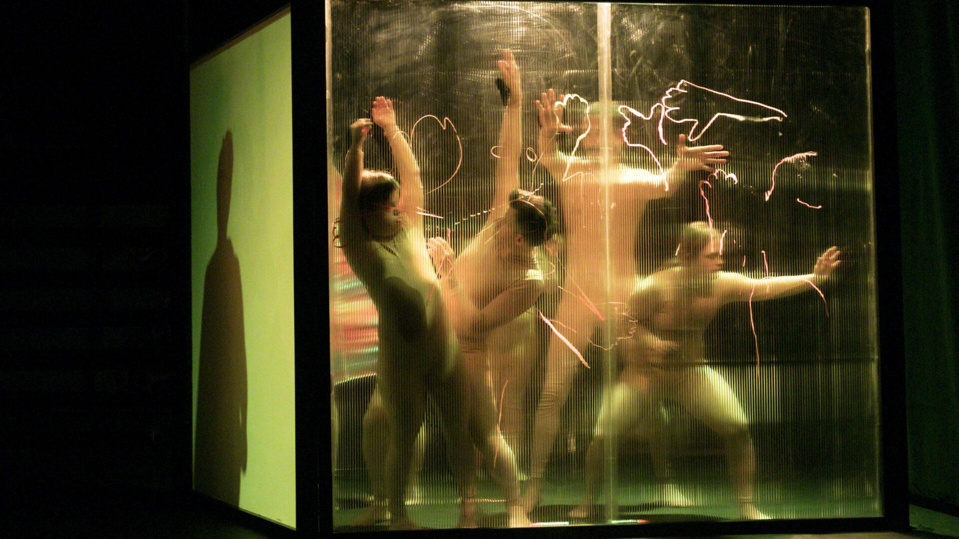 Szenenfoto einer Auffuehrung: Vier Personen hinter einer transparenten Wand auf einer Buehne.